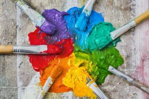 A mixture of different paints with paint brushes