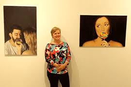 This image shows a professor standing between two works of art composed by students.