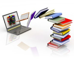 A laptop and books arranged in a stack