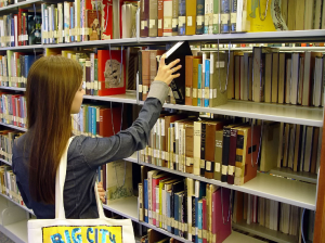 female student checking a book from a library shelf