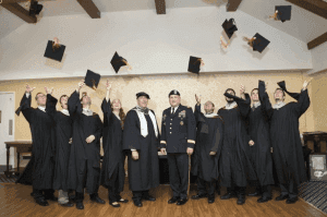 graduate students throwing their cap with their professors