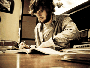 male student writing on a book