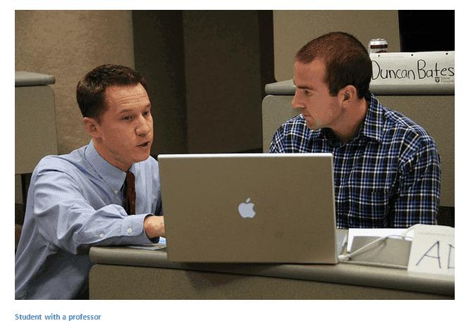 professor showing student something on laptop