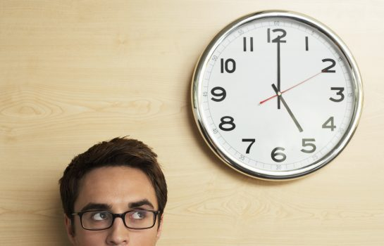 man looking at clock to manage time for exam