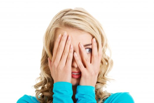 girl with blonde hair covering her eyes except one
