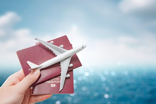 image of person holding two passports and a toy airplane