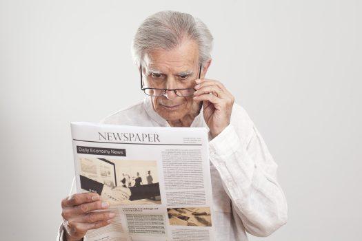 elderly man reading the newspaper