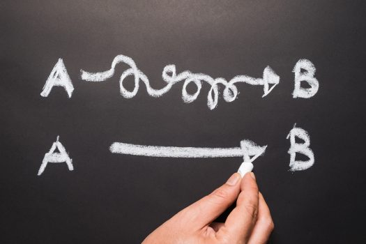 person writing on chalkboard showing a complicated and simple way to get from point a to b