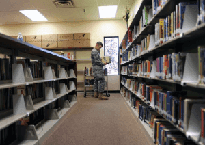 soldier reading book in a library