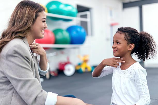 A speech therapist teaching a child
