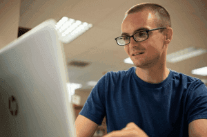 student with glasses using laptop