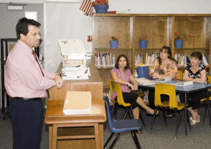 teacher on a desk teaching parents