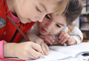 two children drawing on a notebook
