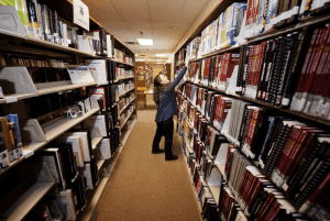 woman looking for books at a library