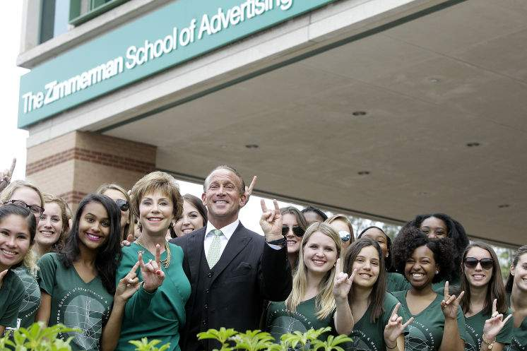 President Genshaft and CEO Jordan Zimmerman pose with students.