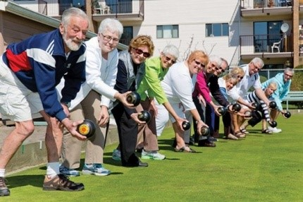 men and women playing indoor lawn bowls