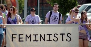 people supporting feminists with banner