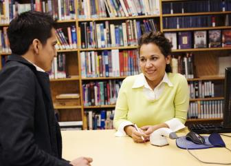 Two people talking in the library