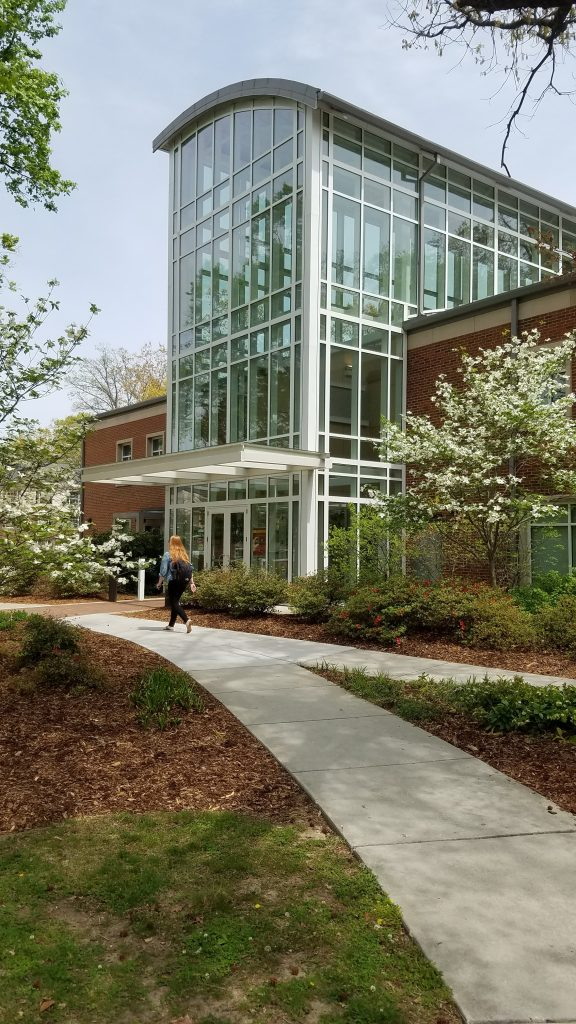 This image shows a student walking into the Student Health Services building.