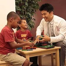 The occupational therapists doing the therapy of two children