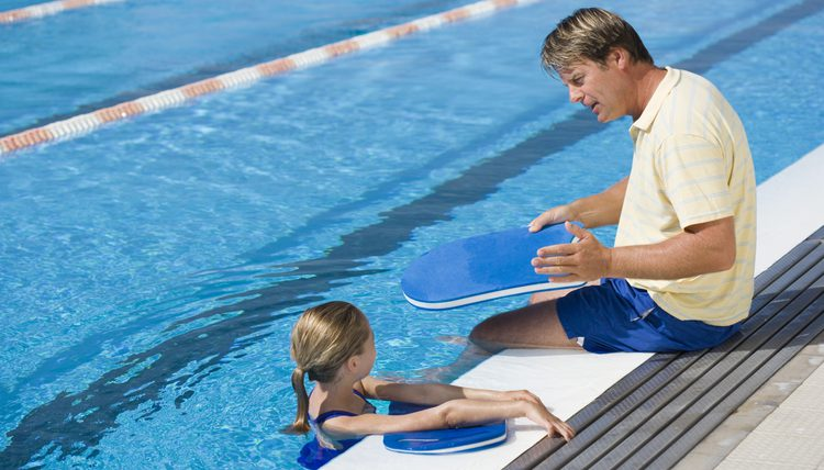 a swim instructor teaching a young swimmer how to swim