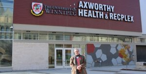 A man standing in front of the Axworthy Health and RecPlex
