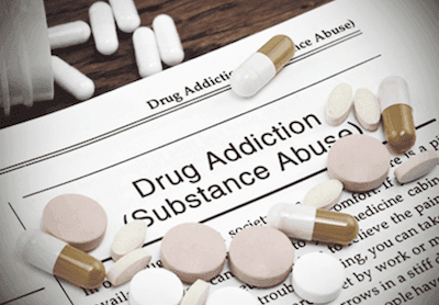 Drug and pills on an article about drug addiction
