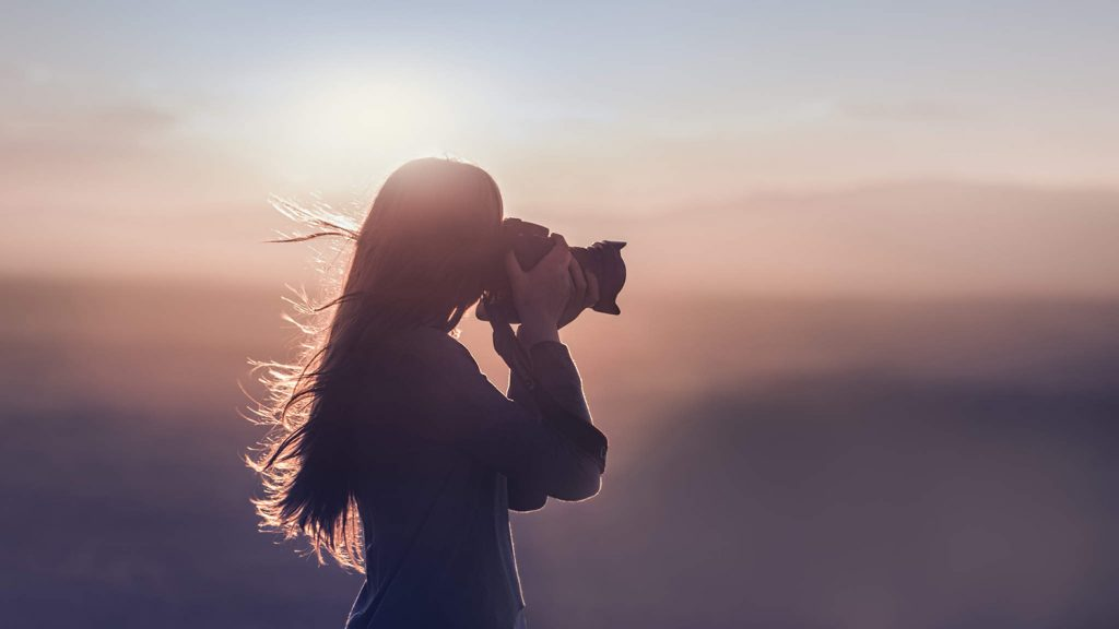 A silhouette of a girl taking a picture with a camera