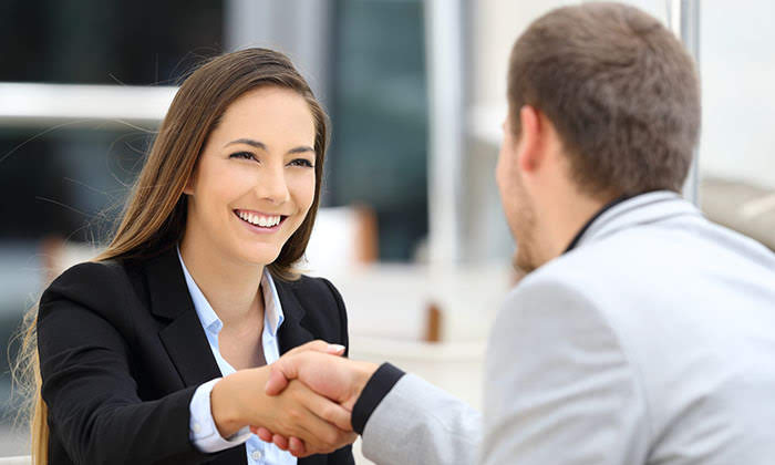 A man and a woman in professional suits shaking hands making business with each other