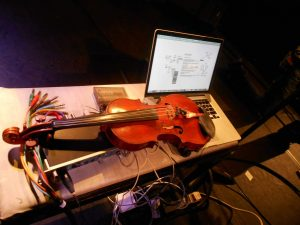 A table with a violin connected to a laptop through cables to record acoustic music