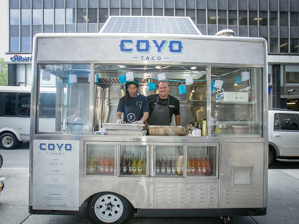 Two employees in a food cart