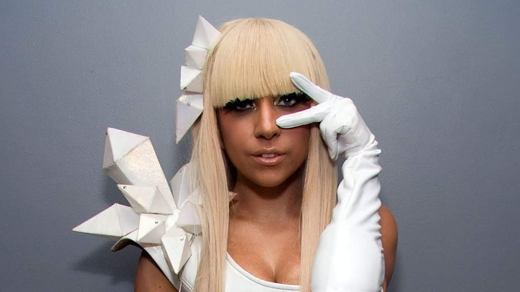 Lady Gaga Using a blonde wig and a white costume making the peace sign with her left hand