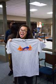 A student holds her SI shirt