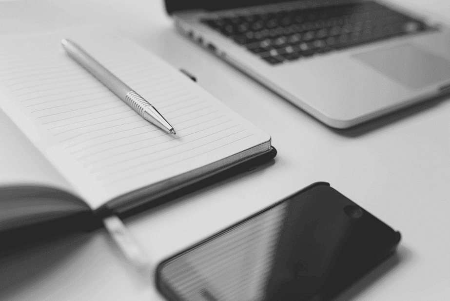 laptop with pen and paper and smartphone