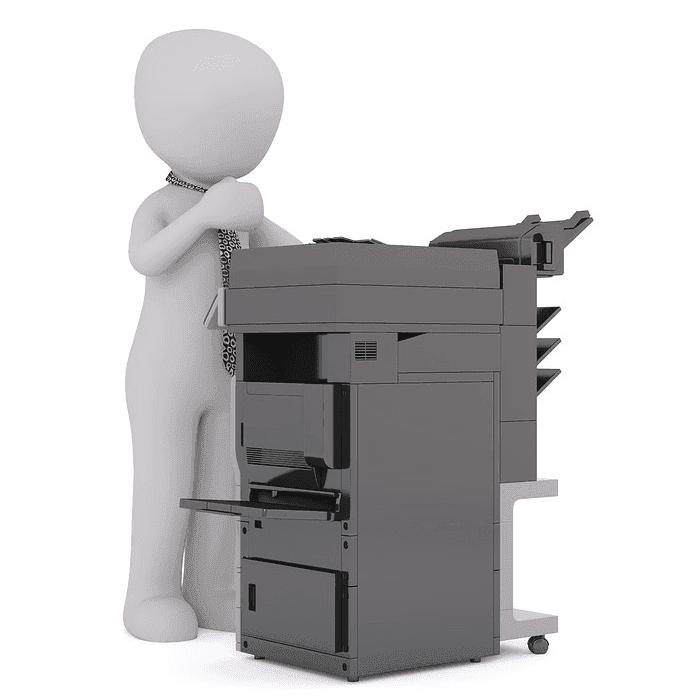 man standing beside a printer