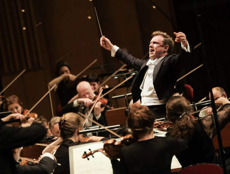 An orchestra director conducting a concert in a theater with his hands up making the violins play