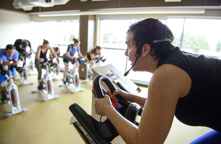 A fitness instructor leading the spin class in training