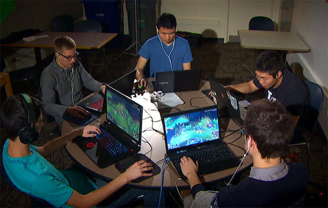 A room with a group of five gamers playing video games seating in a roundtable with laptops