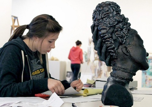 the girl is getting details about the sculpture