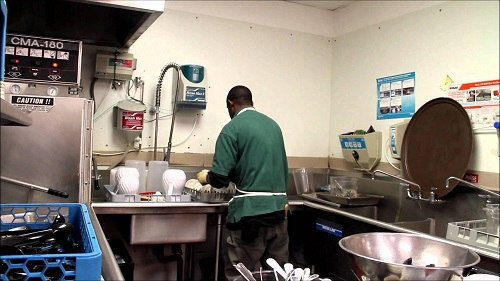 the boy is washing the dishes at the restaurant