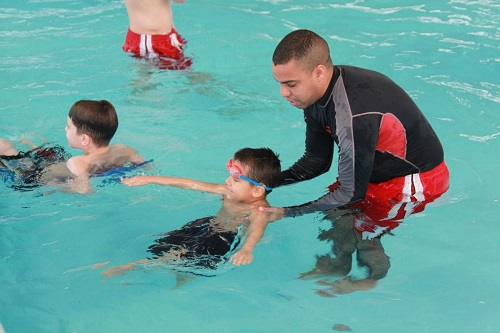 the boy is instructing the children how to swim