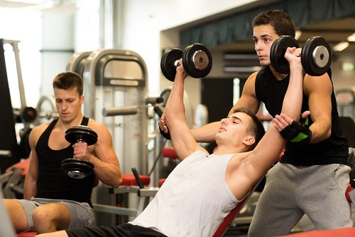 fitness trainer is helping his clients