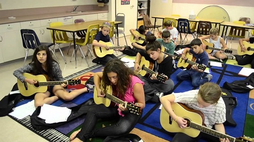 students learning how to play a guitar