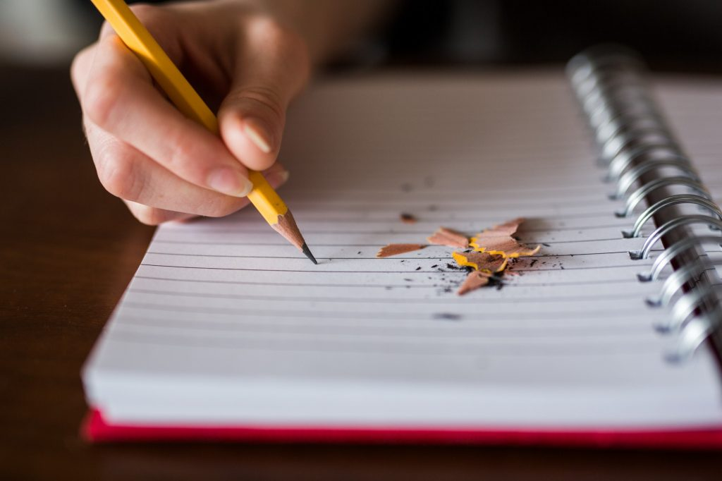 A person writing on a notebook with pencil shavings