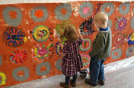 2 kids painting on the wall