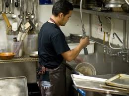 A young man cleaning dishes