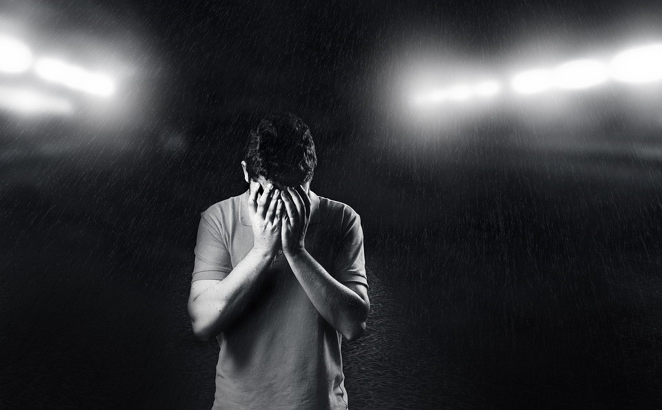 A depressed person covering his face