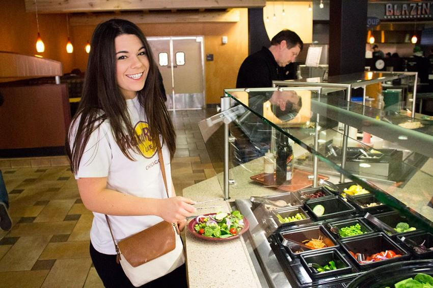 A girl taking a plate of fresh salad from the counter