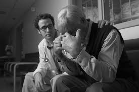 A doctor consoling an old man
