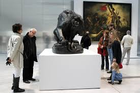A group of people looking at the art piece